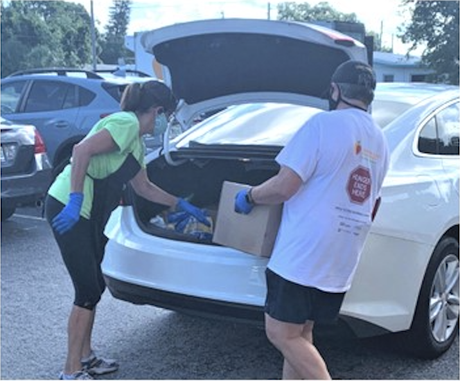 Volunteers loading food into a car.